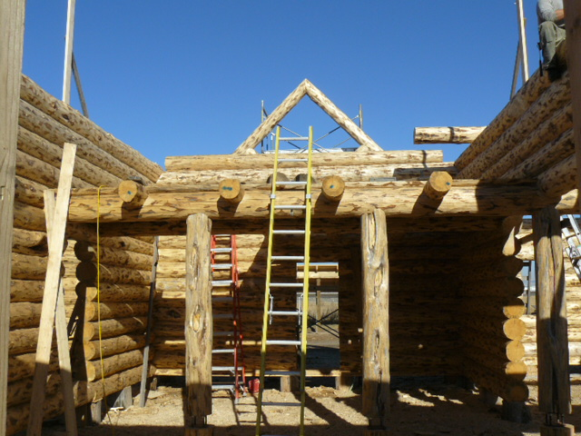 Log truss at entry showing behind full log gable